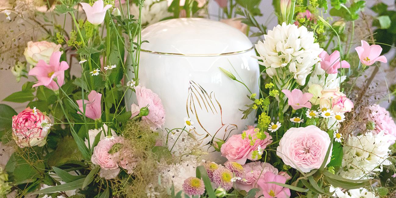 Aufbahrung mit Blütenkranz vor einer Urnenbeisezung